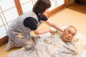 登録ヘルパーが介護者を布団に移動させる画像